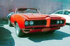 Ένα κόκκινο αμερικανικό εκλεκτής ποιότητας κλασικό μετατρέψιμο αυτοκίνητο που σταθμεύουν σε ένα κατάστημα επισκευής στην οδό της  στοκ φωτογραφία με δικαίωμα ελεύθερης χρήσης