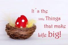 Ένα κόκκινο αυγό Πάσχας στη φωλιά με τη ζωή αναφέρει τα μικρά πράγματα καθιστά τη ζωή μεγάλη Στοκ Εικόνες