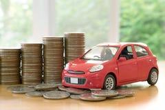 Ένα κόκκινο αυτοκίνητο πέρα από πολλά συσσωρευμένα νομίσματα Στοκ φωτογραφία με δικαίωμα ελεύθερης χρήσης