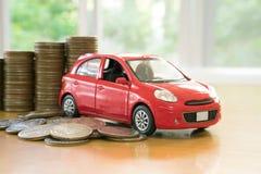 Ένα κόκκινο αυτοκίνητο πέρα από πολλά συσσωρευμένα νομίσματα Στοκ εικόνα με δικαίωμα ελεύθερης χρήσης
