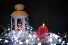 Ένα κόκκινο κερί με τα φω'τα Χριστουγέννων στο ατμοσφαιρικό φως στοκ εικόνες