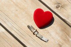 Ένα κόκκινο κιβώτιο βελούδου με ένα ζευγάρι των χρυσών γαμήλιων δαχτυλιδιών Στοκ Φωτογραφία