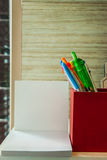 Ένα κόκκινο κιβώτιο των μανδρών είναι εκτός από το άσπρο κενό έγγραφο Στοκ Φωτογραφία