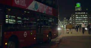 Ένα κόκκινο λεωφορείο του Λονδίνου που τραβά μακρυά από μια στάση λεωφορείου στο Λονδίνο τη νύχτα απόθεμα βίντεο