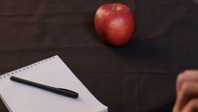 Ένα κόκκινο μήλο βρίσκεται σε ένα μαύρο τραπεζομάντιλο Το χέρι μιας κινηματογράφησης σε πρώτο πλάνο εφήβων καθορίζει ένα σημειωμα απόθεμα βίντεο