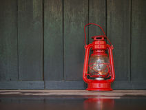 Ένα κόκκινο παλαιό φανάρι στο σκοτεινό υγρό ξύλινο πάτωμα με την αντανάκλαση ο Στοκ εικόνες με δικαίωμα ελεύθερης χρήσης