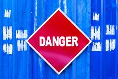 Ένα κόκκινο σημάδι κινδύνου τοποθέτησε σε έναν μπλε τοίχο μετάλλων Στοκ Φωτογραφία