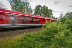 Ένα κόκκινο τραίνο συναγωνίζεται μετά από τη κάμερα στοκ φωτογραφία
