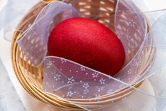 Ένα κόκκινο χρωμάτισε το αυγό Πάσχας βρίσκεται σε ένα ψάθινο καλάθι στοκ εικόνα με δικαίωμα ελεύθερης χρήσης