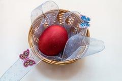 Ένα κόκκινο χρωμάτισε το αυγό Πάσχας βρίσκεται σε ένα ψάθινο καλάθι στοκ φωτογραφία