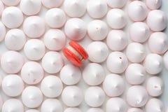 Ένα κόκκινο macaron μεταξύ της άσπρης κρέμας στοκ φωτογραφία