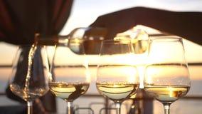 Ένα κόμμα θαλασσίως στο ηλιοβασίλεμα, χύνει το κρασί σε τέσσερα ποτήρια γυαλιού HD, 1920x1080 κίνηση αργή απόθεμα βίντεο