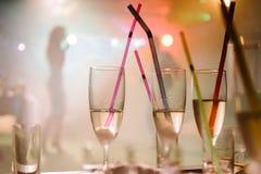 Ένα κόμμα σε ένα νυχτερινό κέντρο διασκέδασης, γυαλιά σαμπάνιας με τα άχυρα Στοκ εικόνες με δικαίωμα ελεύθερης χρήσης