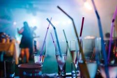 Ένα κόμμα σε ένα νυχτερινό κέντρο διασκέδασης, γυαλιά σαμπάνιας με τα άχυρα Στοκ Εικόνες