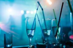 Ένα κόμμα σε ένα νυχτερινό κέντρο διασκέδασης, γυαλιά σαμπάνιας με τα άχυρα Στοκ εικόνα με δικαίωμα ελεύθερης χρήσης