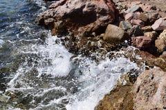 Ένα κύμα θάλασσας με τον αφρό χτυπά την ακτή πετρών Στοκ Φωτογραφία