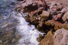 Ένα κύμα θάλασσας με τον αφρό χτυπά την ακτή πετρών Στοκ εικόνες με δικαίωμα ελεύθερης χρήσης