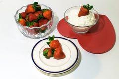 Ένα κύπελλο των φραουλών, και φράουλες στην κρέμα και τα πιάτα στοκ φωτογραφία