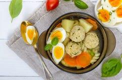 Ένα κύπελλο της σούπας με τις σφαίρες κρέατος κοτόπουλου, λαχανικά, έβρασε το αυγό και το fusilli Στοκ φωτογραφία με δικαίωμα ελεύθερης χρήσης