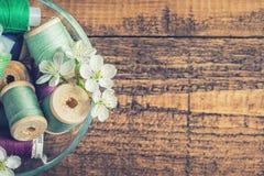 Ένα κύπελλο των ράβοντας νημάτων με τα άνθη στοκ εικόνες