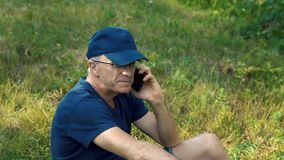 Ένα λεπτό γκρίζος-μαλλιαρό άτομο σε μια μπλε μπλούζα, μια ΚΑΠ και τα γυαλιά μιλά στο τηλέφωνο και το γέλιο, καθμένος στο πράσινο απόθεμα βίντεο