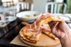 Ένα μάζεμα με το χέρι ένα κομμάτι της πίτσας ζαμπόν της Πάρμας τρώει μέχρι στο εστιατόριο Στοκ Φωτογραφίες