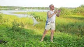Ένα μέσο ηλικίας άτομο κάνει τις ασκήσεις γιόγκας και αναπνοής στη λίμνη το πρωί απόθεμα βίντεο