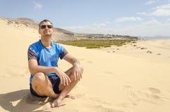 Ένα μέσο ηλικίας άτομο στα γυαλιά ηλίου που κάθεται διαγώνιο με πόδια στην παραλία στοκ εικόνες