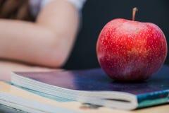 ένα μήλο βρίσκεται σε ένα σημειωματάριο για ένα πρόχειρο φαγητό σε ένα σπάσιμο Στοκ εικόνα με δικαίωμα ελεύθερης χρήσης
