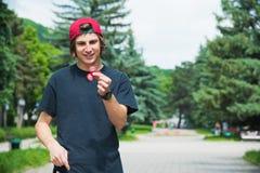 Ένα μακρυμάλλες hipster σε μια ΚΑΠ κάθεται σε έναν πάγκο και περιστρέφει έναν fidget-κλώστη Στοκ εικόνες με δικαίωμα ελεύθερης χρήσης