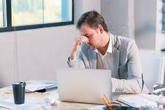 Ένα ματαιωμένο άτομο εργάζεται πίσω από ένα lap-top, λόγω των προβλημάτων που κρατούν το κεφάλι του Μέσα στο γραφείο Στοκ εικόνες με δικαίωμα ελεύθερης χρήσης