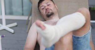 Ένα ματαιωμένο άτομο με μια γενειάδα εναπόκειται σε ένα επιδεμένο πόδι απόθεμα βίντεο