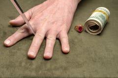 Ένα μαχαίρι μεταξύ των δάχτυλων ενός ανθρώπινου χεριού στο υπόβαθρο των δολαρίων και ενός χρυσού δαχτυλιδιού στοκ φωτογραφίες με δικαίωμα ελεύθερης χρήσης