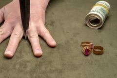 Ένα μαχαίρι μεταξύ των δάχτυλων ενός ανθρώπινου χεριού στο υπόβαθρο των δολαρίων και του χρυσού κοσμήματος στοκ φωτογραφίες με δικαίωμα ελεύθερης χρήσης