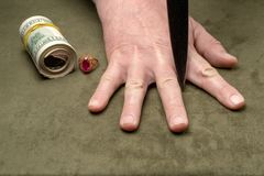 Ένα μαχαίρι μεταξύ των δάχτυλων ενός ανθρώπινου χεριού στο υπόβαθρο των δολαρίων και ενός χρυσού δαχτυλιδιού στοκ εικόνα με δικαίωμα ελεύθερης χρήσης