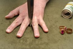 Ένα μαχαίρι μεταξύ των δάχτυλων ενός ανθρώπινου χεριού στο υπόβαθρο των δολαρίων και του χρυσού κοσμήματος E στοκ εικόνες