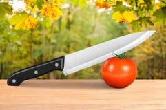 Ένα μαχαίρι που κόβει την κόκκινη ντομάτα Στοκ φωτογραφίες με δικαίωμα ελεύθερης χρήσης