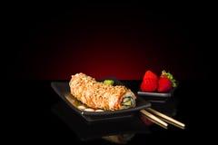 Ένα μαύρο πιάτο με τους ιαπωνικούς ρόλους και τις φράουλες σουσιών Έννοια σουσιών Στοκ φωτογραφία με δικαίωμα ελεύθερης χρήσης