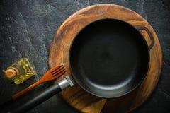 Ένα μαύρο τηγανίζοντας τηγάνι χυτοσιδήρων για το μαγείρεμα των τροφίμων λαχανικό καρυκευμάτων π&epsi Στοκ Εικόνα