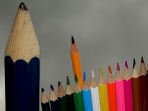 Ένα μεγάλο ατημέλητο μολύβι, που στέκεται παράλληλα με μια μικρή ομάδα έξυπνων αιχμηρών χρωματισμένων μολυβιών στοκ εικόνες