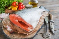 Ένα μεγάλο κομμάτι του σολομού βρίσκεται σε έναν ξύλινο πίνακα για το μαγείρεμα με ένα μαχαίρι και μια συσκευή για τα ψάρια καθαρ Στοκ Εικόνες
