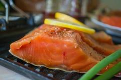 Ένα μεγάλο κομμάτι του σολομού που μαρινάρεται με το λεμόνι βρίσκεται σε έναν ξύλινο πίνακα για το μαγείρεμα Οριζόντιο πλαίσιο Στοκ Εικόνα