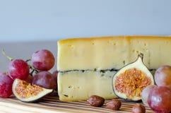 Ένα μεγάλο κομμάτι του τυριού, σταφύλια, καρύδια, τεμάχισε τα σύκα στο ξύλινο tabl Στοκ εικόνες με δικαίωμα ελεύθερης χρήσης