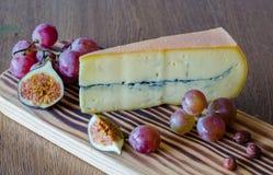 Ένα μεγάλο κομμάτι του τυριού, σταφύλια, τεμάχισε τα σύκα στην ξύλινη επιτραπέζια πλάτη Στοκ φωτογραφία με δικαίωμα ελεύθερης χρήσης