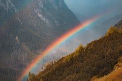 Ένα μεγάλο όμορφο ουράνιο τόξο μετά από μια βροχή σε ένα υπόβαθρο του βουνού Στοκ Φωτογραφία