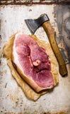 Ένα μεγάλο κομμάτι του ακατέργαστου χοιρινού κρέατος με ένα τσεκούρι κρέατος Στοκ εικόνα με δικαίωμα ελεύθερης χρήσης