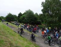 Ένα μεγάλο πλήθος των αναβατών ποδηλάτων σε μια εθνική οδό δίπλα σε ένα ανάχωμα Στοκ εικόνα με δικαίωμα ελεύθερης χρήσης