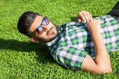 Ένα Μεσο-Ανατολικό άτομο μόδας με τη γενειάδα, ύφος τρίχας μόδας στηρίζεται στον όμορφο πράσινο χρόνο ημέρας χλόης Στοκ Φωτογραφία