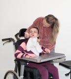 Ένα με ειδικές ανάγκες παιδί σε μια αναπηρική καρέκλα μαζί με έναν εθελοντή εργαζόμενο προσοχής Στοκ Φωτογραφίες