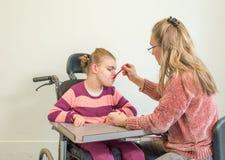 Ένα με ειδικές ανάγκες παιδί σε μια αναπηρική καρέκλα μαζί με έναν εθελοντή εργαζόμενο προσοχής Στοκ εικόνα με δικαίωμα ελεύθερης χρήσης